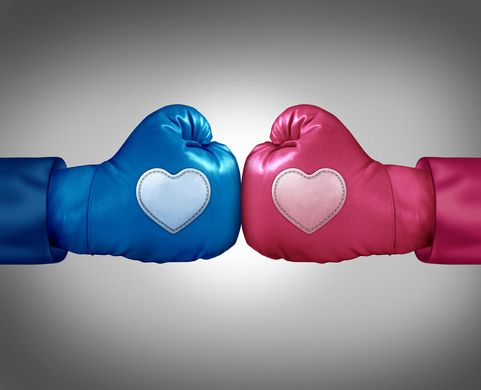 Fighting for love and relationship argument concept as blue and pink boxing gloves with heart shaped patches face off in a passionate couple dispute resulting in stress and possible separation or divorce.